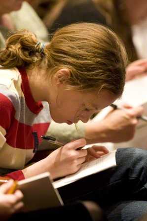 A girl with a light brown ponytail bends her head down as she writes in a notebook that is open on her lap.