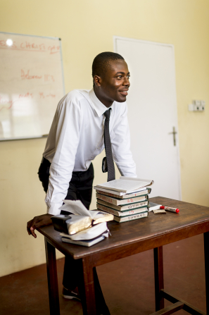 A male Sunday School teacher stands at the front of a classroom and leans his hands on a table where hymnbooks and his scriptures are stacked.