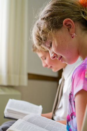 A girl sits next to a boy, and both have a set of scriptures open on their laps as they read from them while sitting in a classroom.