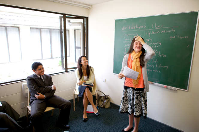 A young woman with long brown hair and a scarf around her neck puts her hand on her head and laughs while sharing a comment with her classmates.