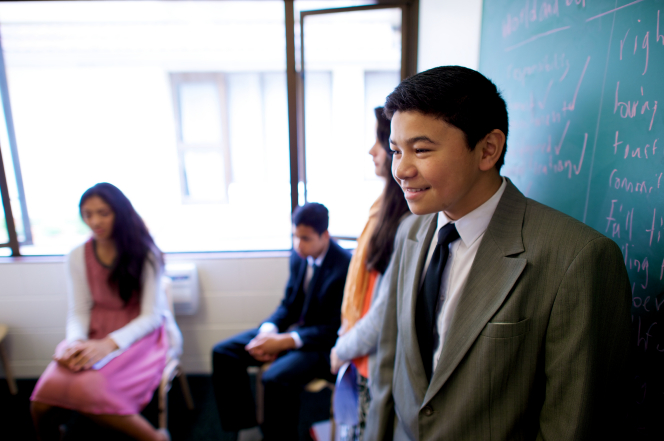 A young man in a suit and tie stands at the front of a classroom next to a chalkboard and talks to a room of young men and young women.