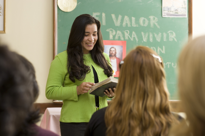 A woman with long brown hair, wearing a green cardigan, stands at the front of a classroom near a chalkboard and reads from scriptures open in her hands.