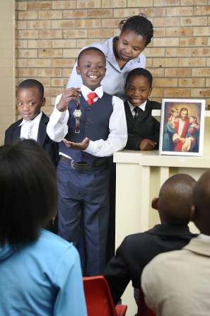 A young boy in a vest, tie, and slacks shows a watch during sharing time while standing beside two boys and his teacher.