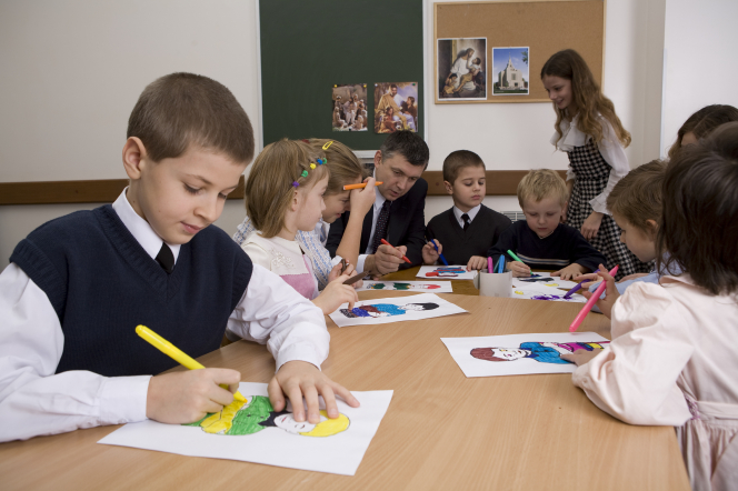 Four young boys and five young girls sit around a table and color a picture during a Primary class with the teacher at the head of the table.