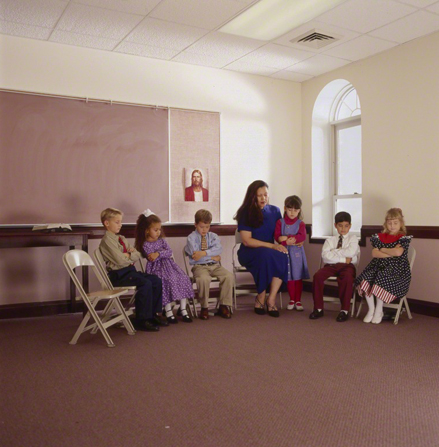 A female Primary teacher sits on a fold-out chair next to a girl who is standing and folding her arms while praying with four children in a classroom.
