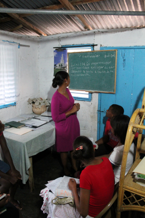 A woman in a dark purple dress stands in a small room next to a chalkboard and teaches seminary to three students, all sitting down in front of her.