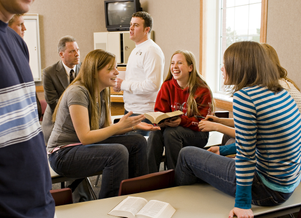 A group of four young women face each other and discuss something from the scriptures together in a classroom with desks.