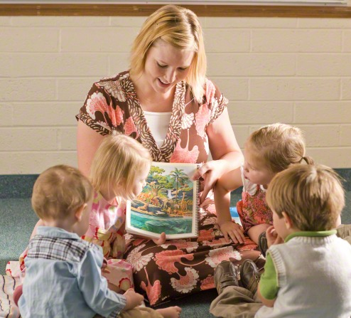 A woman in a pink and brown dress with short blond hair kneels on the floor with four small children and tells them a story from the Bible.