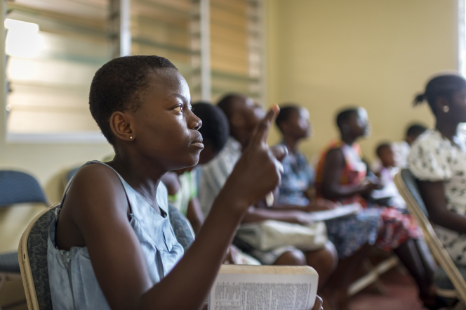 A young woman raises her hand during Sunday School with her scriptures open on her lap and other students sitting around her in the classroom.