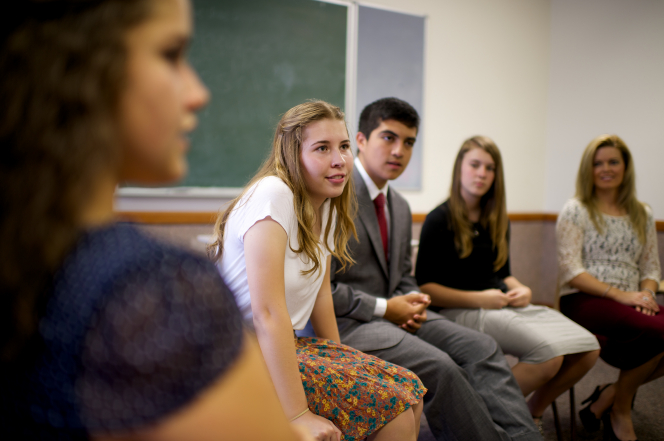 A young woman with long blond hair, wearing a skirt, leans forward in her chair and looks to the front of the classroom with other young men and women.