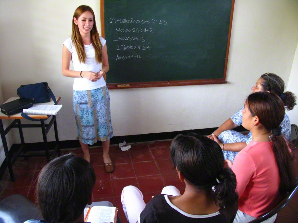 A young woman with long brown hair and in a skirt stands at the front of a classroom next to a blackboard and teaches to a room of five young women.
