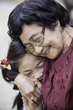 A portrait of an elderly woman hugging her young granddaughter.