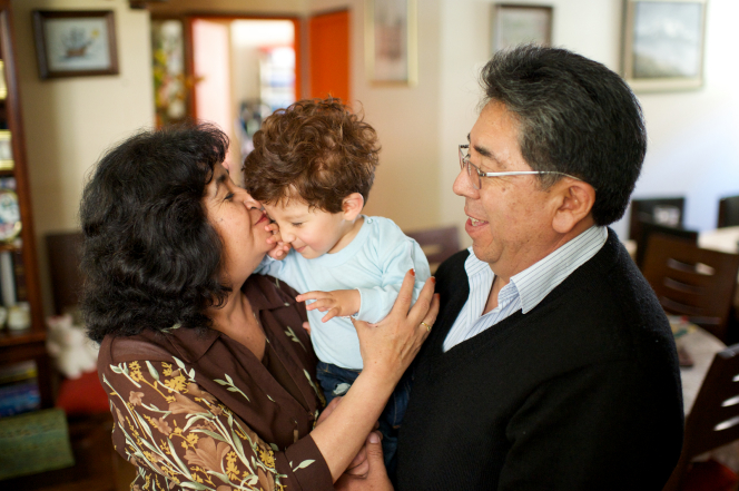 Grandparents holding a small boy in Bolivia.