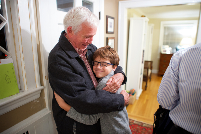 An elderly man gives his grandson a hug in the entryway of the house.