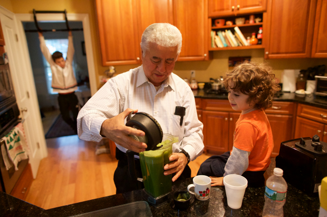 A man in a white shirt making a green smoothie for his grandson.