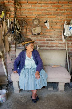 An informal portrait of an elderly woman in a hat sitting outside.