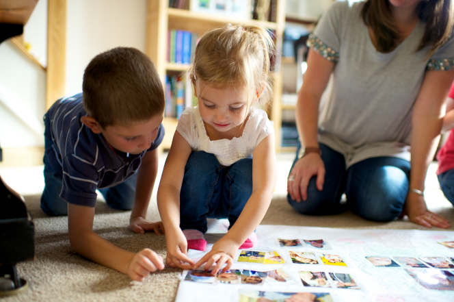 A boy and a girl kneel down in a living room by their mother and make a family tree with family photos.