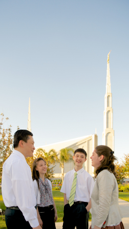 A family of four gathers and talks outside the Buenos Aires Argentina Temple on a sunny day.