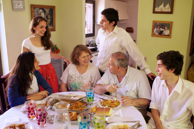 A mother and father sit at the dinner table with their four teenage children.