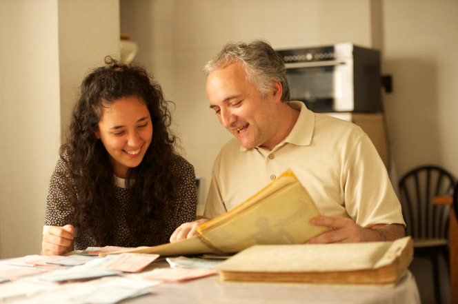 A father and daughter sit down at a table and look at family history documents together.