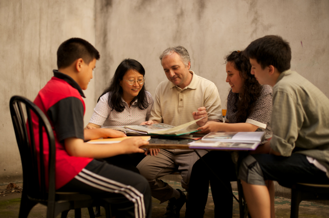 A father, mother, daughter, and two sons from Argentina sit at a table and look through family history documents.