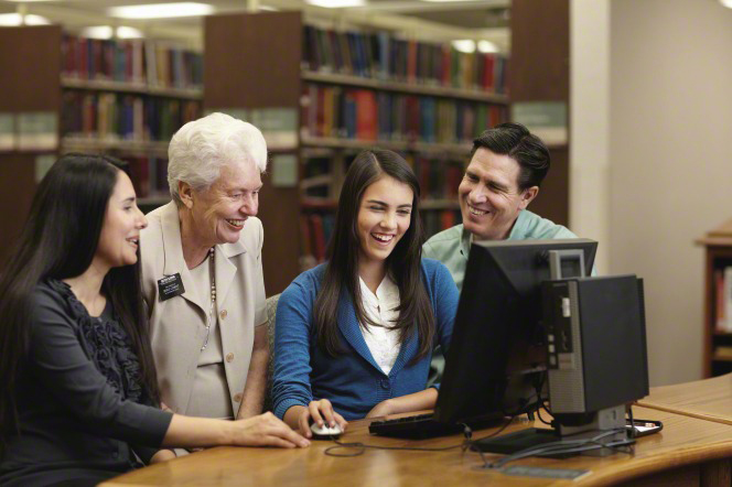 A senior sister missionary assists a family sitting and doing family history research at a table in a library.
