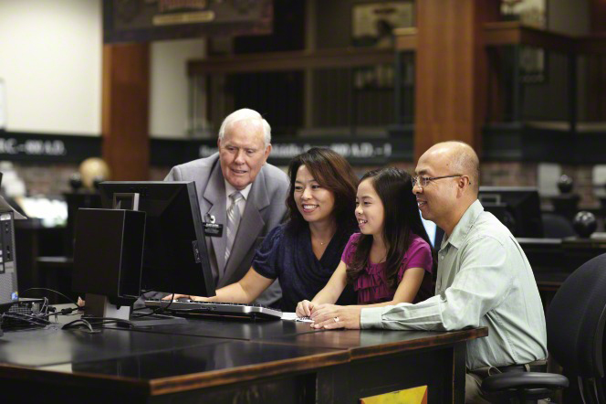 A senior elder missionary helps a young family at the computer do family history research.
