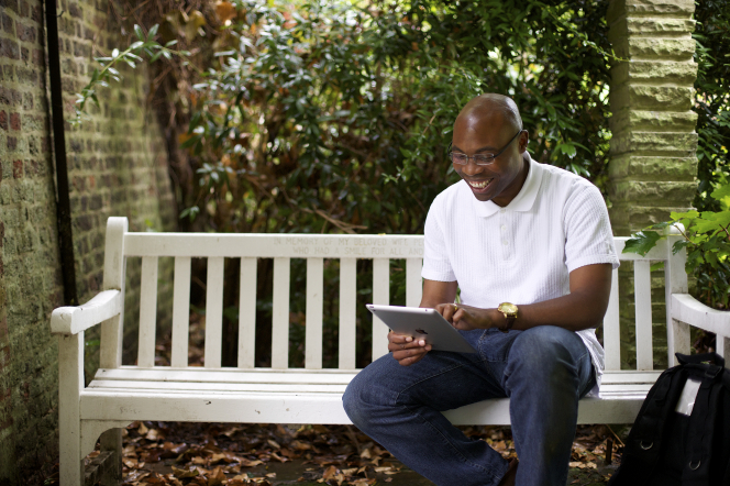 A man in a white shirt, jeans, and glasses sits outside on a white bench and looks at family history on his tablet.