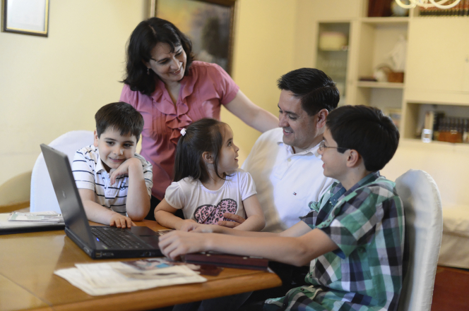 A father, mother, and three children from Argentina gather around a laptop sitting on a table as they work on family history together.