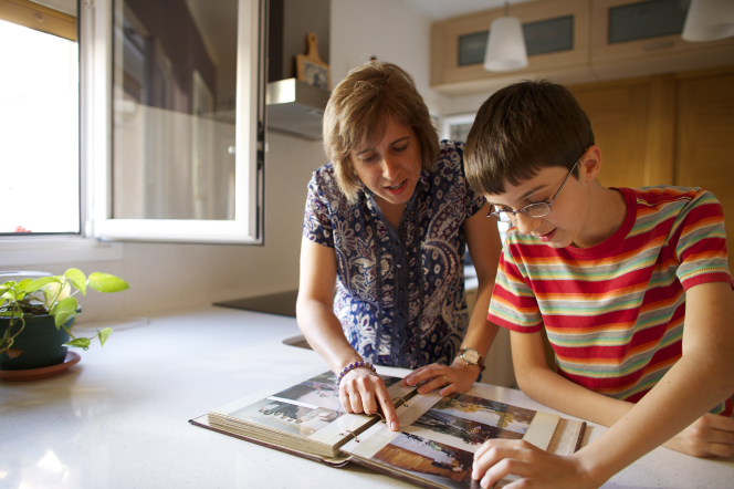 A grandmother looks at family pictures in a photo album with her grandson at the kitchen counter.