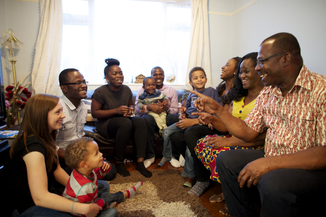 An extended family sits and talks together in a living room during a family home evening.