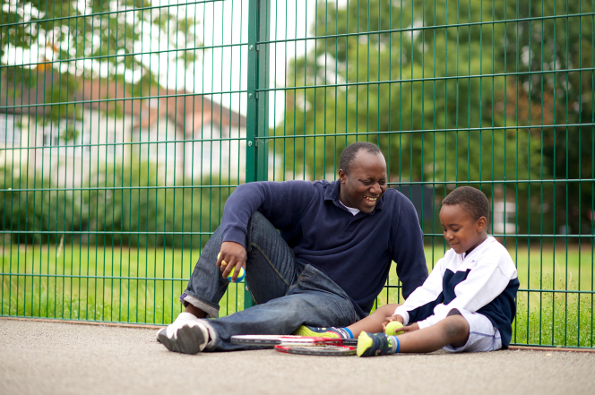 A father sits down next to his young son in a tennis court, with two tennis rackets beside them.