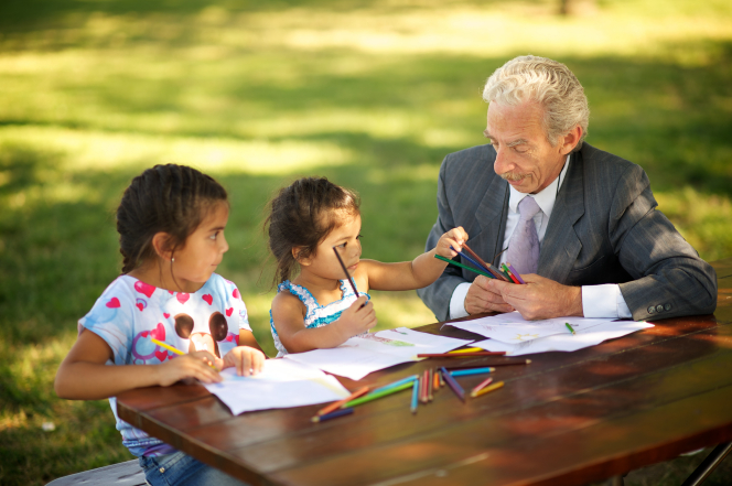 A grandfather sits outside at a picnic table and colors with his two young granddaughters.