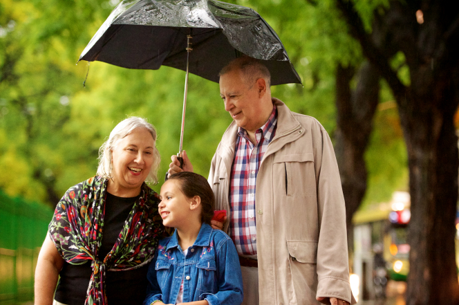 Two grandparents hold an umbrella while walking with their young granddaughter in the rain.