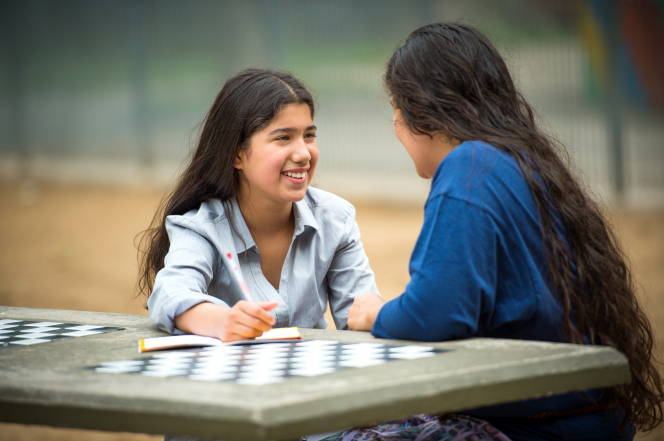 A mother with long brown hair sits and talks with her daughter in a gray blouse at a table in a park.