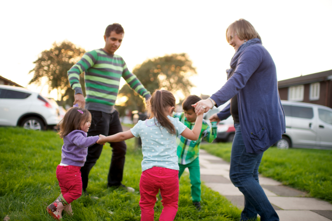 "A father, mother, son, and two daughters stand in a circle outside, hold hands, and play ""Ring around the Rosie."""
