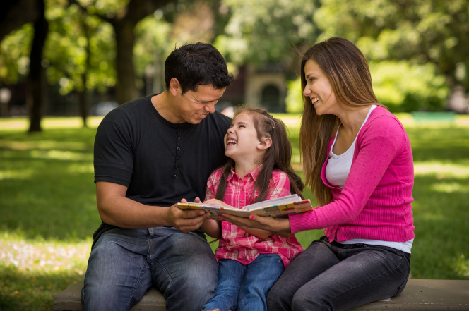 A mother and father sit on a bench in the park, with their daughter sitting between them, and look through a family album.