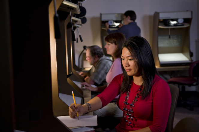 A young woman sits and looks on a microfilm reader while doing family history research.