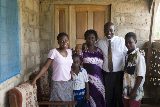 A mother and father stand and smile with their three children.
