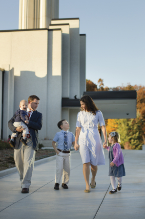 Two parents walk with their three young children on temple grounds.