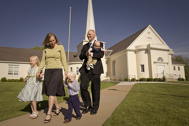 A mother holds hands with two of her children as they walk near a Church building. Her husband is carrying their third child.