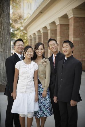 A mother and father smile with their three teenage children on Temple Square.