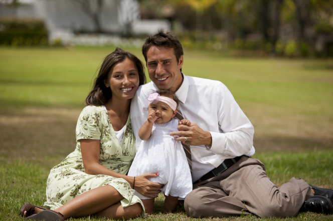 A husband and wife sit on the grass together with their baby daughter.