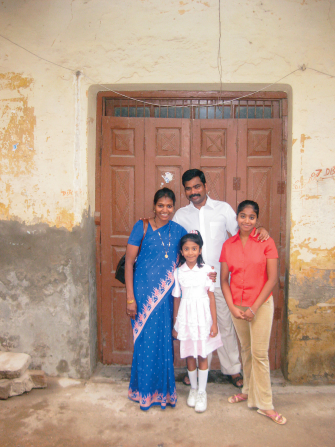 A mother and father stand in front of a door with their two children.