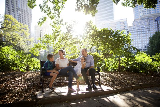 A mother and father sit on a bench in a park with their two children.
