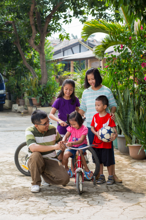 A father helps his little daughter on a bike. A mother stands nearby with another daughter and their son, who is holding a soccer ball.