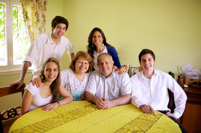 A mother and father sit at the dining room table with their four grown children.