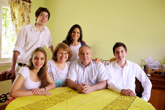 Two parents and four adult children sit together at a table in their home, which is decorated with yellows and greens.