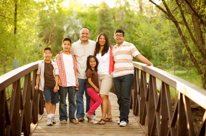 A portrait of a family standing together on a bridge.