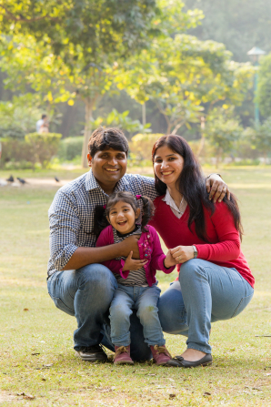 A husband and wife in the park with their toddler-age daughter, smiling.